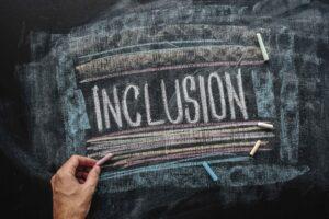 teacher-writing-word-inclusion-on-school-blackboar-4ZMNF8S (1)