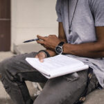 man sitting holding a notepad and writting